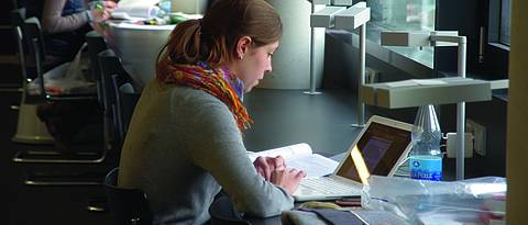 Picture of a studying women in the library.