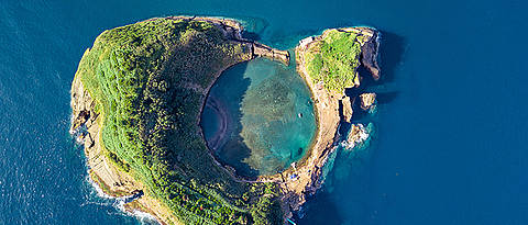 An island of the Azores: It is an example of an underwater volcano that has reached the sea surface. The crater is clearly visible.