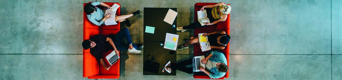 Top view of university students sitting in a library with books and laptop. Young people studying together at college library.